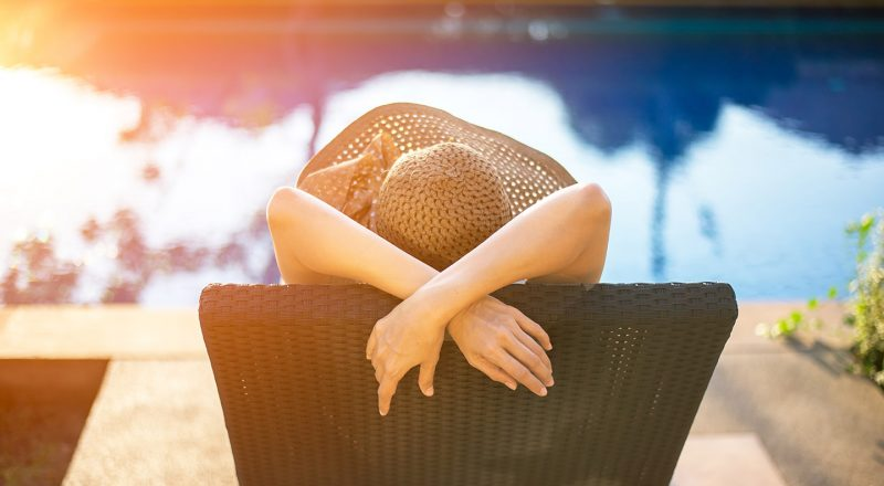 girl in hat relaxing by the pool side sitting on a deck chair